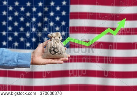 The Concept Of Economic Growth In The Country United States Of America. Hand Holds A Bag With Money