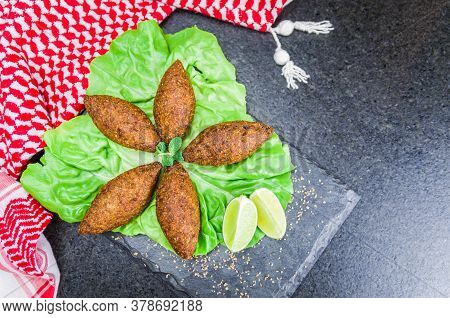 Delicious Lebanese  Food, Kibbeh (kibe) With Sauces And Lemon On Black Slate Stone And Granite Backg