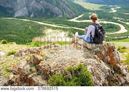 Woman With Backpack Enjoying Breathtaking View Of The Landscape From The Top Of Mountain.