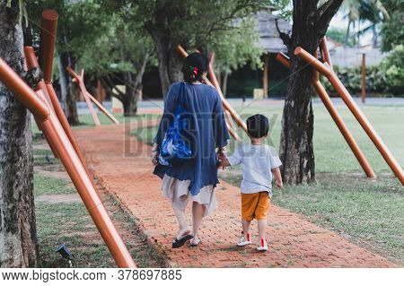 Mother Holding Hand Of His Son Walking In The Park In Summer.