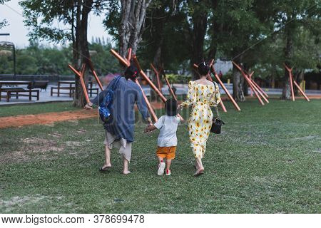 Family Holding Hand Of Young Boy Walking In The Park.