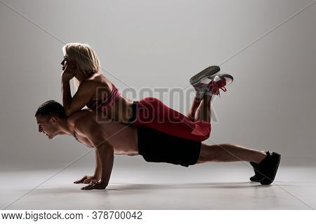 Young Sportsman Doing Push-ups With Female Personal Trainer Lying On His Back