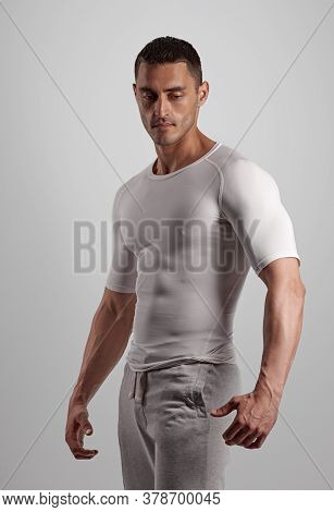 Portrait Of Strong Handsome Athlete Posing In White Sportswear