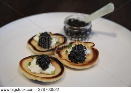 Russian Pancakes Or Blini With Sour Cream And Black Sturgeon Caviar With A Full Jar Of Caviar With A