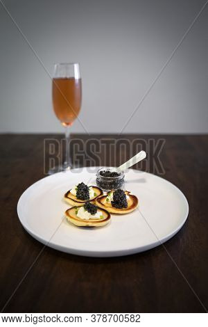 Russian Pancakes Or Blini With Sour Cream And Black Sturgeon Caviar, A Full Jar Of Caviar With A Mot