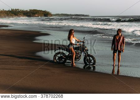 Couple On A Motorbike On The Beach. A Couple In Love On The Beach Meets The Sunset. Beautiful Couple