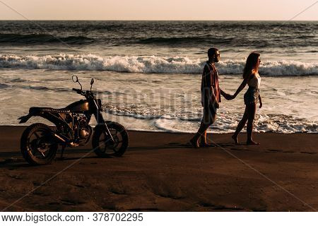 A Man And A Woman Meet The Sunset On The Island Of Bali. A Couple In Love On The Beach Meets The Sun