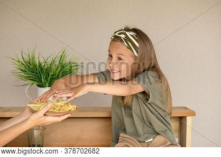 A Small Beautiful Preschool Girl With A Smile Stretches Her Hands To A Plate Of French Fries That Is