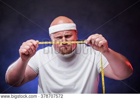 A Plump Bald Man In A White T-shirt Looks At A Measuring Tape In His Hands, Standing On The Blue Con