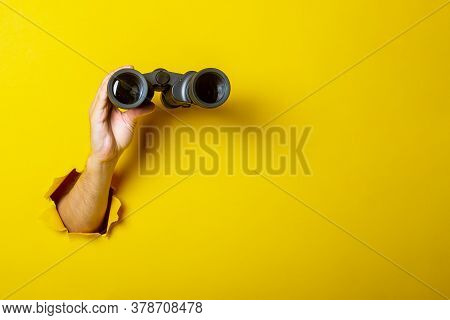 Female Hand Holds Black Binoculars On A Yellow Background. Looking Through Binoculars, Journey, Find