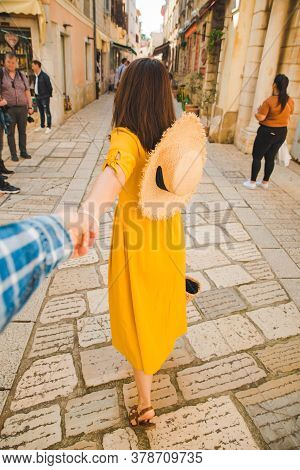 Follow Me Concept. Woman In Yellow Sundress In Straw Hat Walking Forward By Small Resort City Street