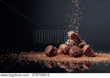 Chocolate Candies On A Black Background Sprinkled With Chocolate Chips. Copy Space.