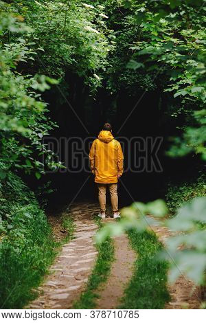 Man In Yellow Raincoat Sanding In Front Of Dark Entrance To The Forest