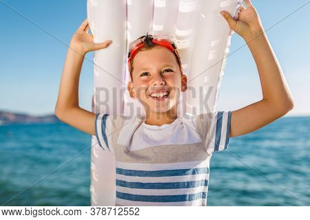 Boy Holding Inflatable Mattresses In Summer At Sea