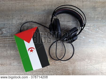 Headphones And Book. The Book Has A Cover In The Form Of Western Sahara Flag. Concept Audiobooks. Le