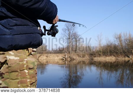 Fishing Rod In The Hands Of A Fisherman On The Lake. Fishermans Hands With Spinning On The Backgroun