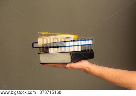 A Stack Of Books In Your Hand, A Day Of Books, Several Books On One Hand On A Neutral Background. Ho