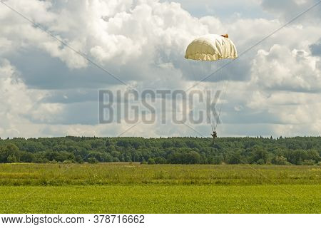 Skydiver Paratrooper In Parachute Dome Lands In The Set Area To Land Situated In The Field Among The