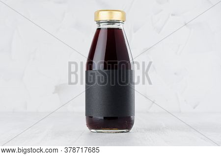Red Cherry Juice In Glass Bottle With Gold Cap And Black Blank Label Mock Up On White Wood Table In