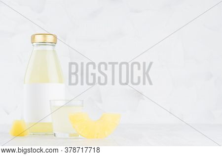 Yellow Muddy Pineapple Juice In Glass Bottle Mock Up With Blank Label, Wine Glass, Fruit Slice On Wh