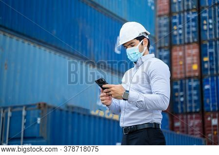 Business Man Wearing Protective Mask To Protect Against Covid-19 Worker Checking Container Box With