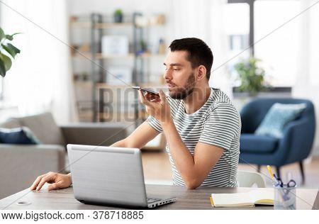 technology, remote job and people concept - man with laptop computer calling on smartphone or using voice command recorder at home office