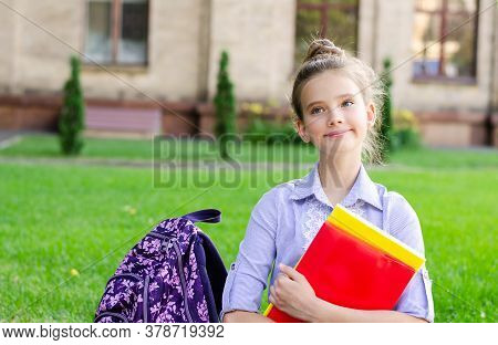 Back To School. Education Concept. Cute Smiling Schoolgirl Sitting On A Grass Near The School. Happy