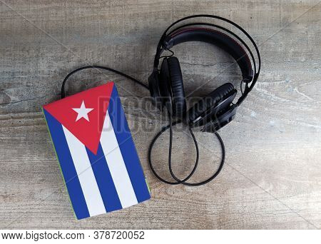 Headphones And Book. The Book Has A Cover In The Form Of Cuba Flag. Concept Audiobooks. Learning Lan