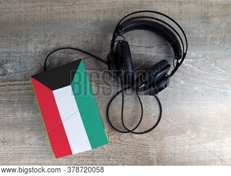 Headphones And Book. The Book Has A Cover In The Form Of Kuwait Flag. Concept Audiobooks. Learning L