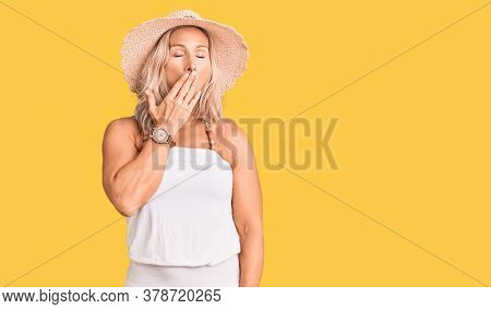 Middle age fit blonde woman wearing summer hat bored yawning tired covering mouth with hand. restless and sleepiness.