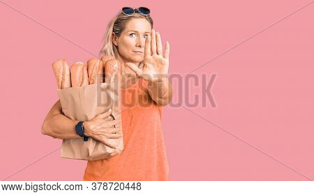 Middle age fit blonde woman holding paper bag with bread with open hand doing stop sign with serious and confident expression, defense gesture