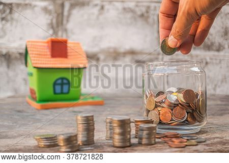 The Hand Of A Man Putting Coins In Glasses Placed On Wood And Old Concrete Background. Money-saving