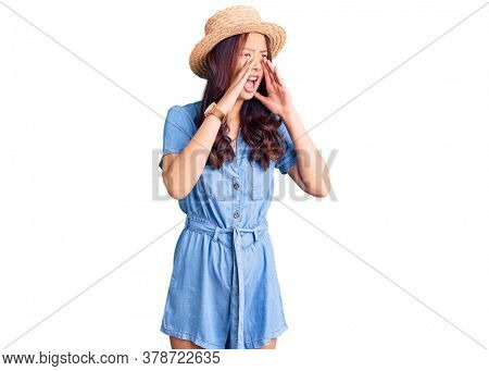 Young beautiful chinese girl wearing summer hat shouting angry out loud with hands over mouth