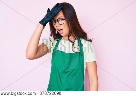 Young beautiful chinese girl wearing cleaner apron surprised with hand on head for mistake, remember error. forgot, bad memory concept.