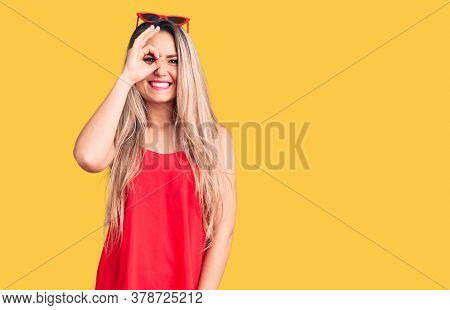 Young beautiful blonde woman wearing sleeveless t-shirt and sunglasses doing ok gesture with hand smiling, eye looking through fingers with happy face.