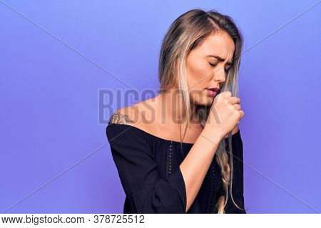 Young beautiful blonde woman wearing casual t-shirt standing over isolated purple background feeling unwell and coughing as symptom for cold or bronchitis. Health care concept.