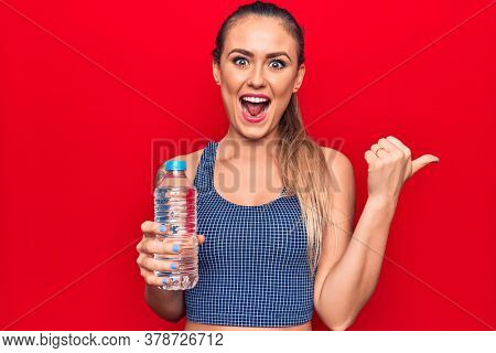 Young beautiful blonde woman drinking bottle of water over isolated red background pointing thumb up to the side smiling happy with open mouth