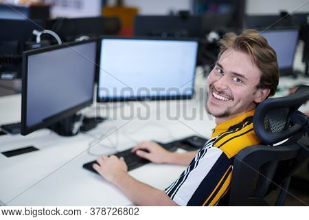 casual business man working on desktop computer in modern open plan startup office interior