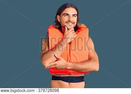 Young handsome man wearing nautical lifejacket with hand on chin thinking about question, pensive expression. smiling with thoughtful face. doubt concept.