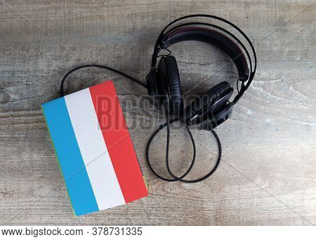 Headphones And Book. The Book Has A Cover In The Form Of Luxembourg Flag. Concept Audiobooks. Learni