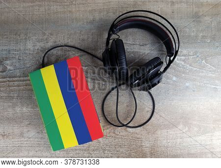 Headphones And Book. The Book Has A Cover In The Form Of Mauritius Flag. Concept Audiobooks. Learnin