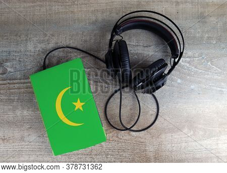 Headphones And Book. The Book Has A Cover In The Form Of Mauritania Flag. Concept Audiobooks. Learni