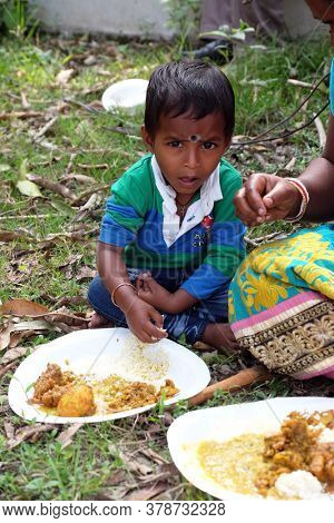 KUMROKHALI, INDIA - FEBRUARY 23, 2020: A young boy eats lunch sitting on the ground in Kumrokhali village, West Bengal, India