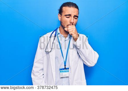 Young handsome man wearing doctor coat and stethoscope feeling unwell and coughing as symptom for cold or bronchitis. health care concept.