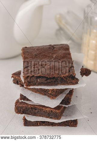 A stack of chocolate brownies with parchment paper between placed on white background. Delicious dessert.