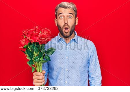 Young handsome blond romantic man holding bouquet of beautiful roses over red background scared and amazed with open mouth for surprise, disbelief face