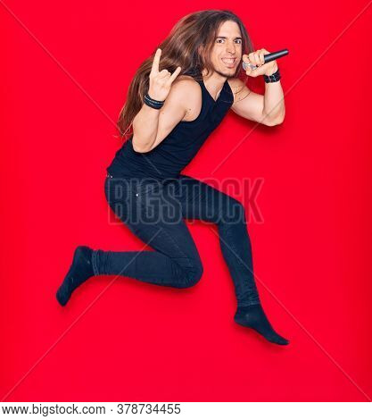 Young handsome heavy singer man with long hair and aggressive expression. Singing song using microphone jumping over isolated red background.