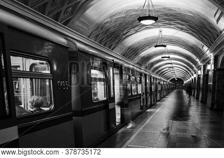 Subway Car And Platform With Silhouettes Of Moving People. Black And White Photograph Of A Subway Pl