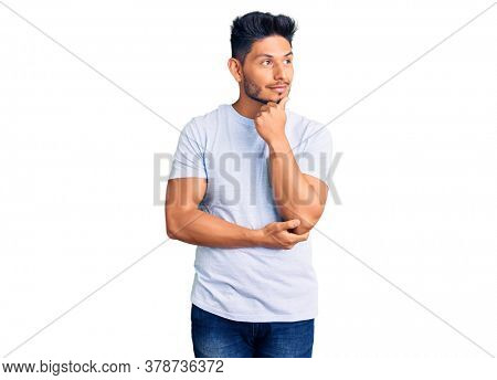 Handsome latin american young man wearing casual clothes with hand on chin thinking about question, pensive expression. smiling with thoughtful face. doubt concept.