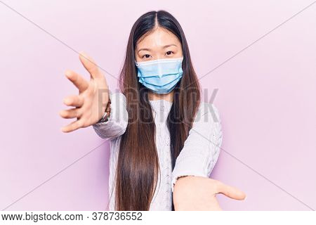 Young beautiful chinese woman wearing medical mask looking at the camera smiling with open arms for hug. cheerful expression embracing happiness.